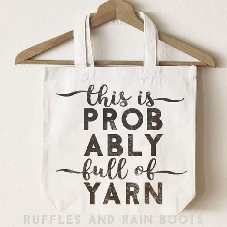 Probably Full of Yarn Knitting SVG on a canvas bag hanging on a wooden hanger