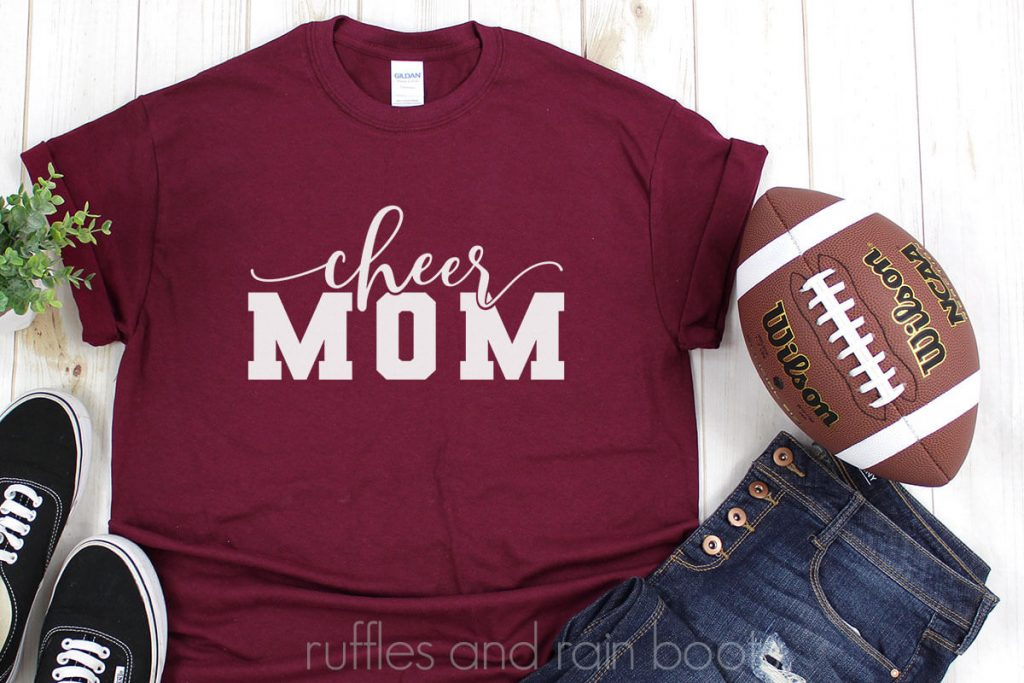 adorable cheer mom svg file for Cricut on a red tshirt with jeans and a football on a white table