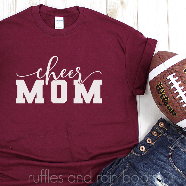 Cheer Mom SVG for football season on a red tshirt with jeans and a football on a white wood table
