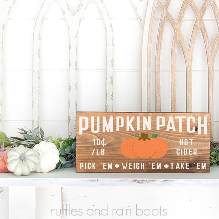 Mounded Pumpkin Patch SVG on a wood sign sittin gon a mantel with some pumpkins in front of a white background
