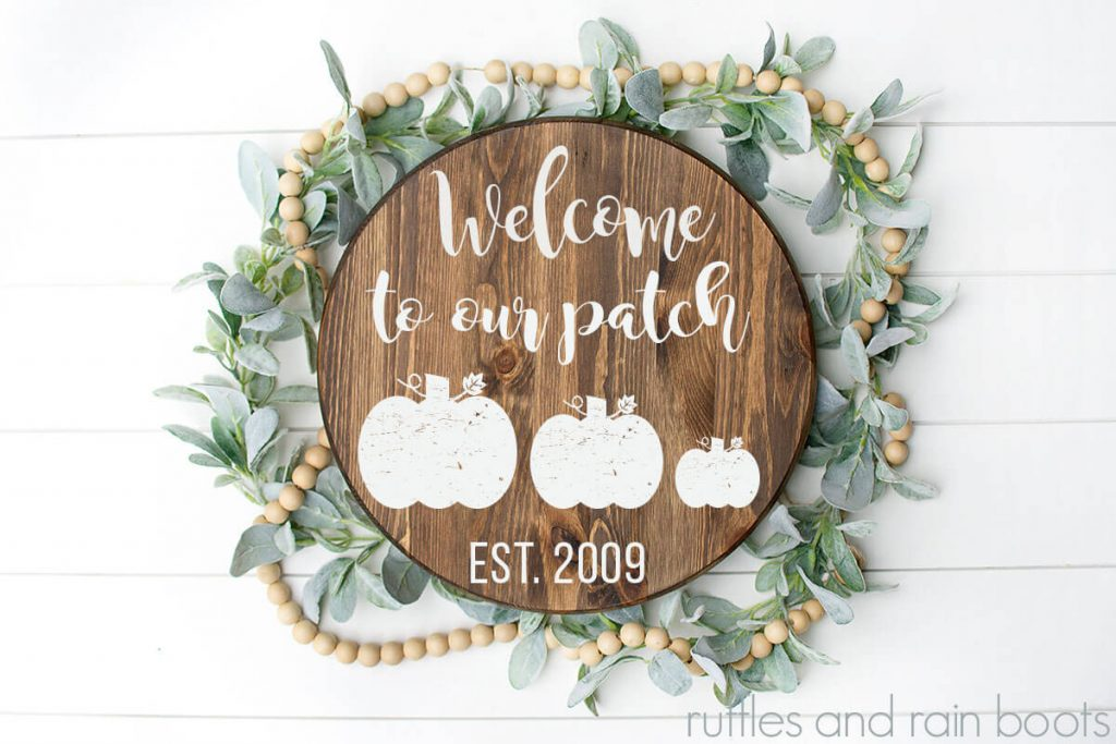 Welcome to Our Patch Pumpkin Cut Files for Free on a wood round sign with some fall floral and wooden beads on a white background