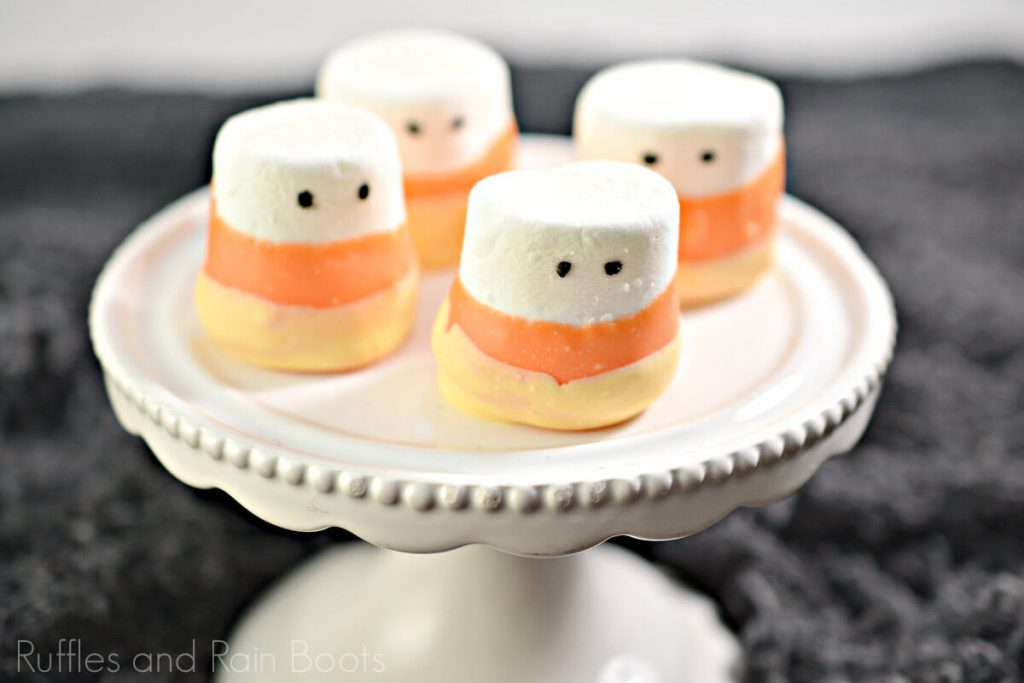 Candy Corn Dipped Marshmallows for Halloween on a white cupcake platter on a black background