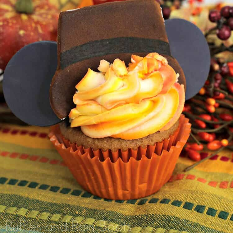 square close up image of adorable Thanksgiving Mickey ear cupcake with a spiced cake and ombre frosting technique on fall background