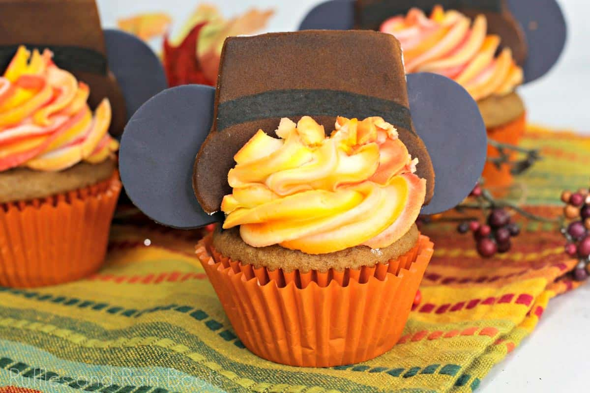 three Thanksgiving Mickey cupcakes with pilgrim hat and mickey mouse ears in fondant with orange ombre frosting on fall background