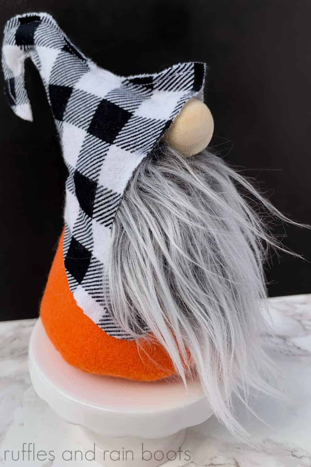 close up of Halloween gnome with buffalo check hat and orange felt body on a pedestal on black background