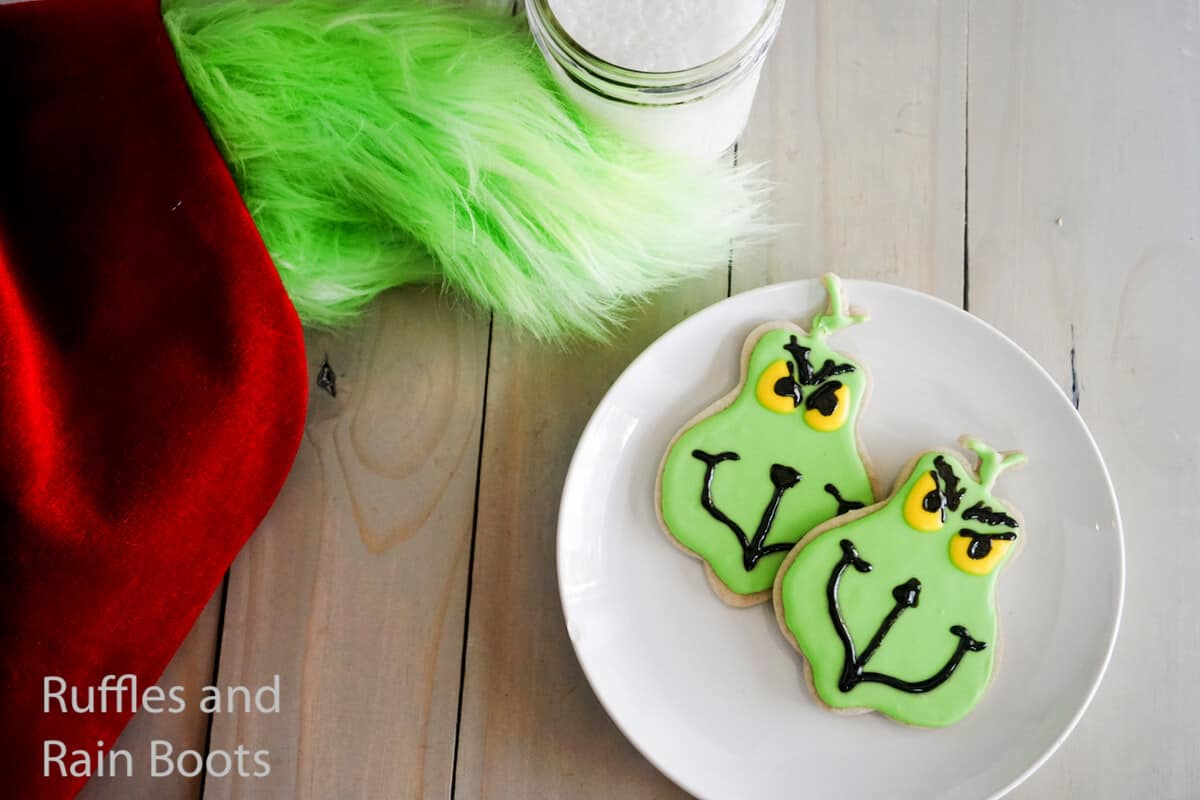 how to make grinch flood cookies on a white plate on a grey wood table