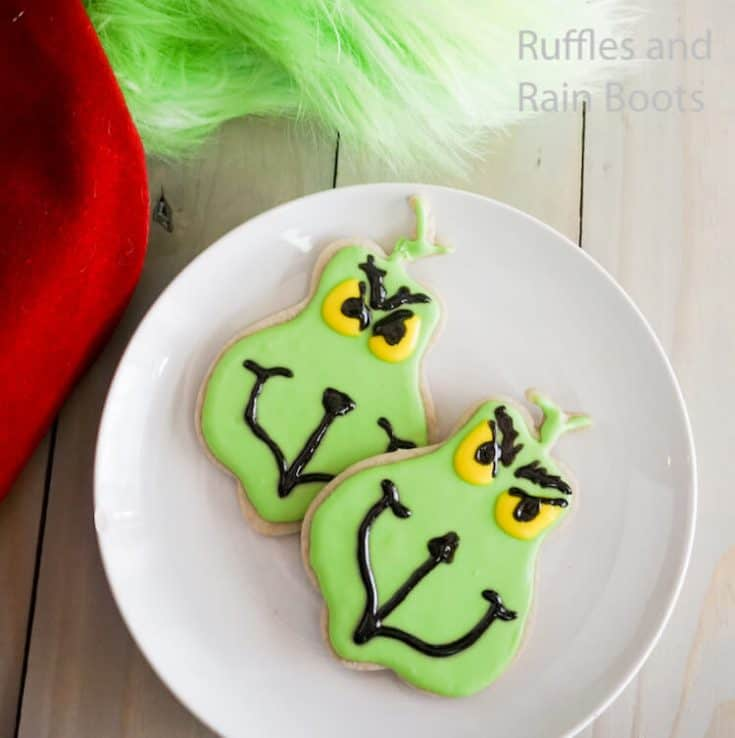 how to make grinch iced cookies on a white plate on a grey wood table