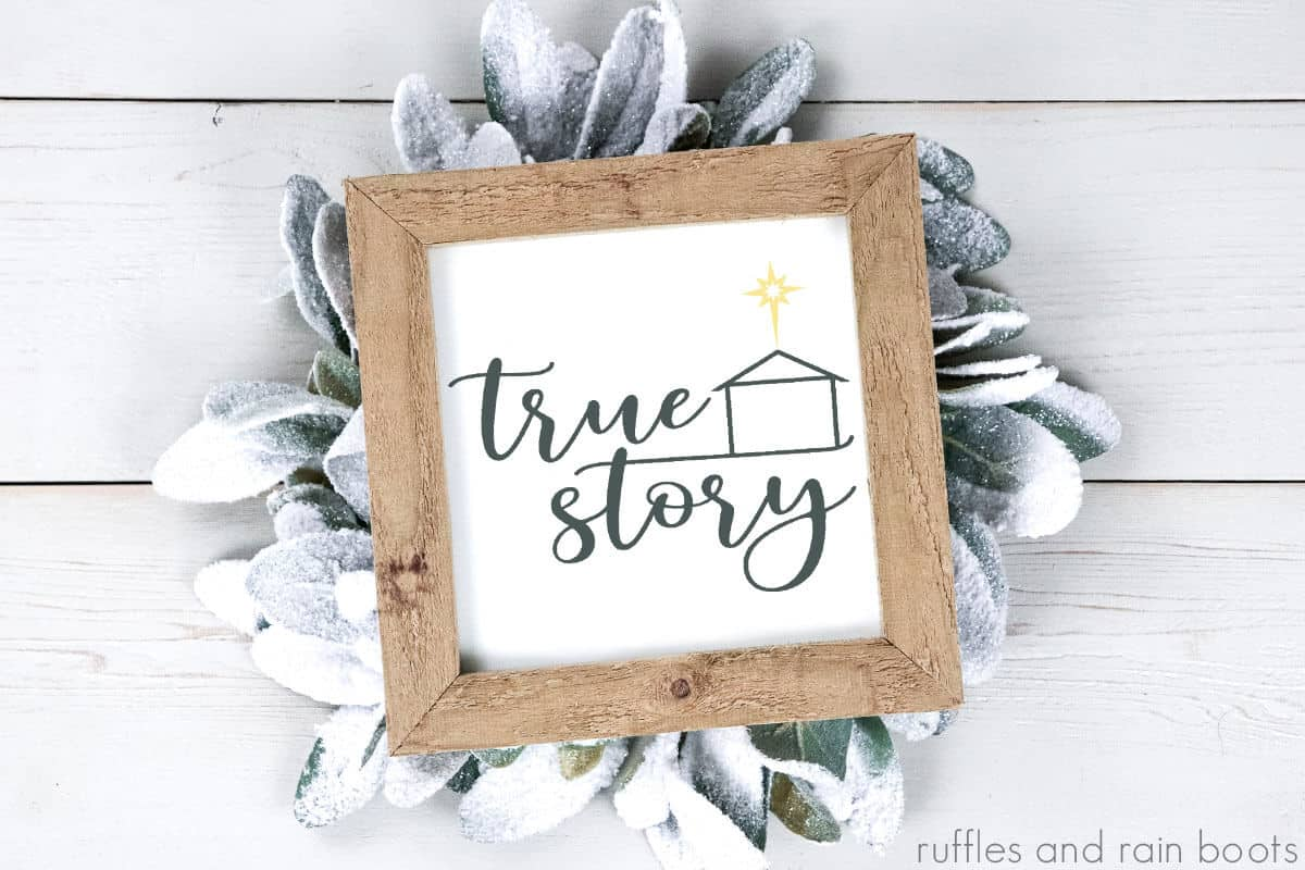 true story svg cut file in dark gray on white and wood framed canvas with frosted leaves on white wood background