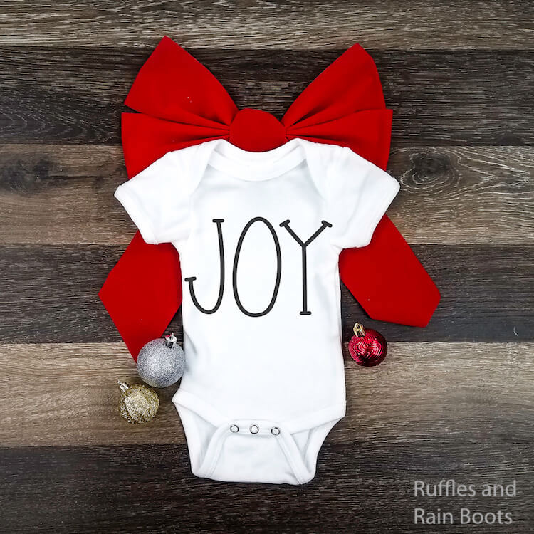 rae dunn inspired joy christmas svg for cricut or silhouette on a baby onesie laying on a red bow on a brown wood background
