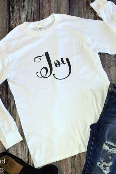 flourish Joy Christmas SVG on a long-sleeved Shirt with jeans and a pair of shoes on a dark brown wood background