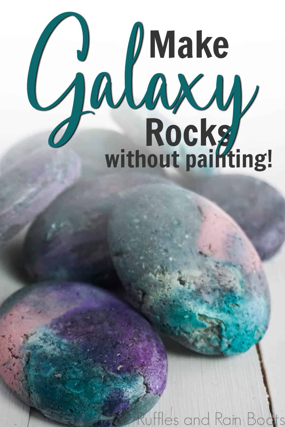 side view of black pink blue and purple rocks on a white table with text which reads make galaxy rocks without painting