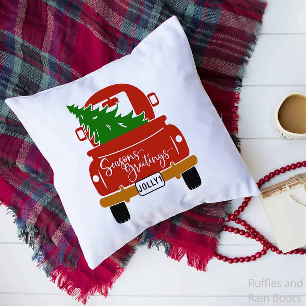 pillow with the christmas back of truck svg on a blanket on a white background