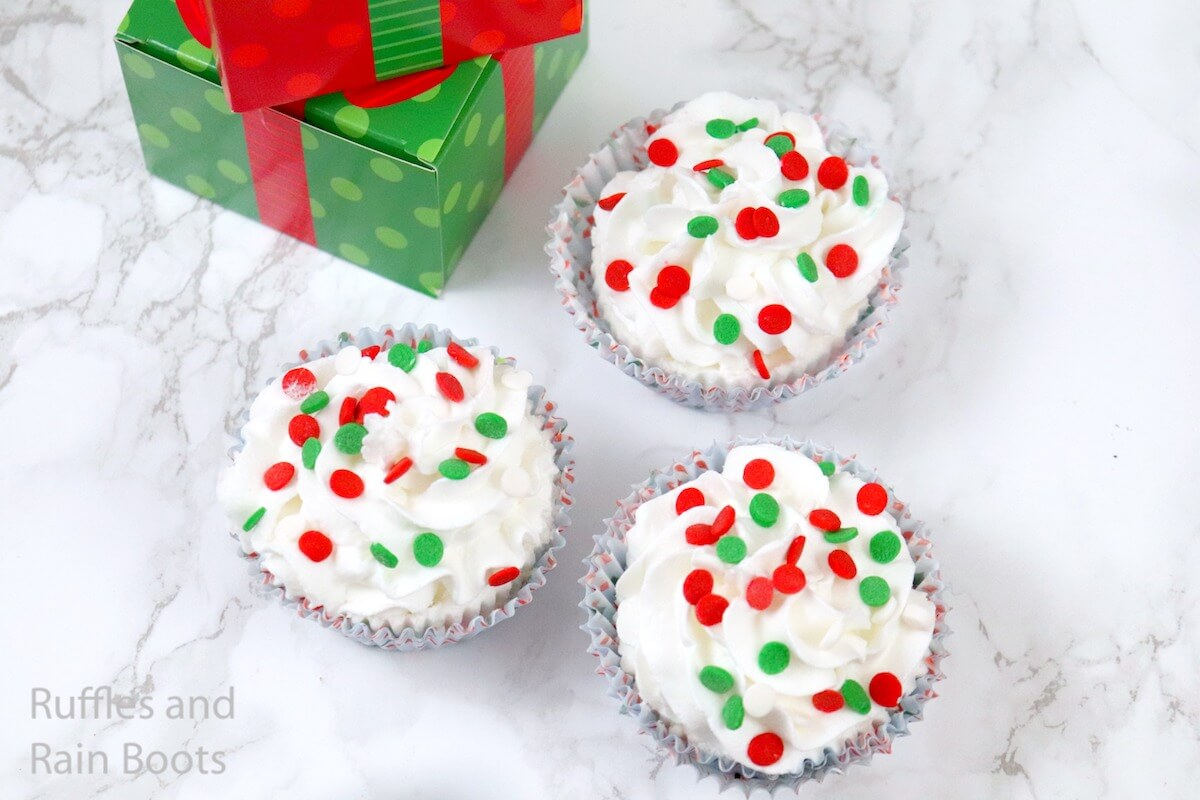 overhead view of how to make christmas cupcake bath bombs on a white background with a green present