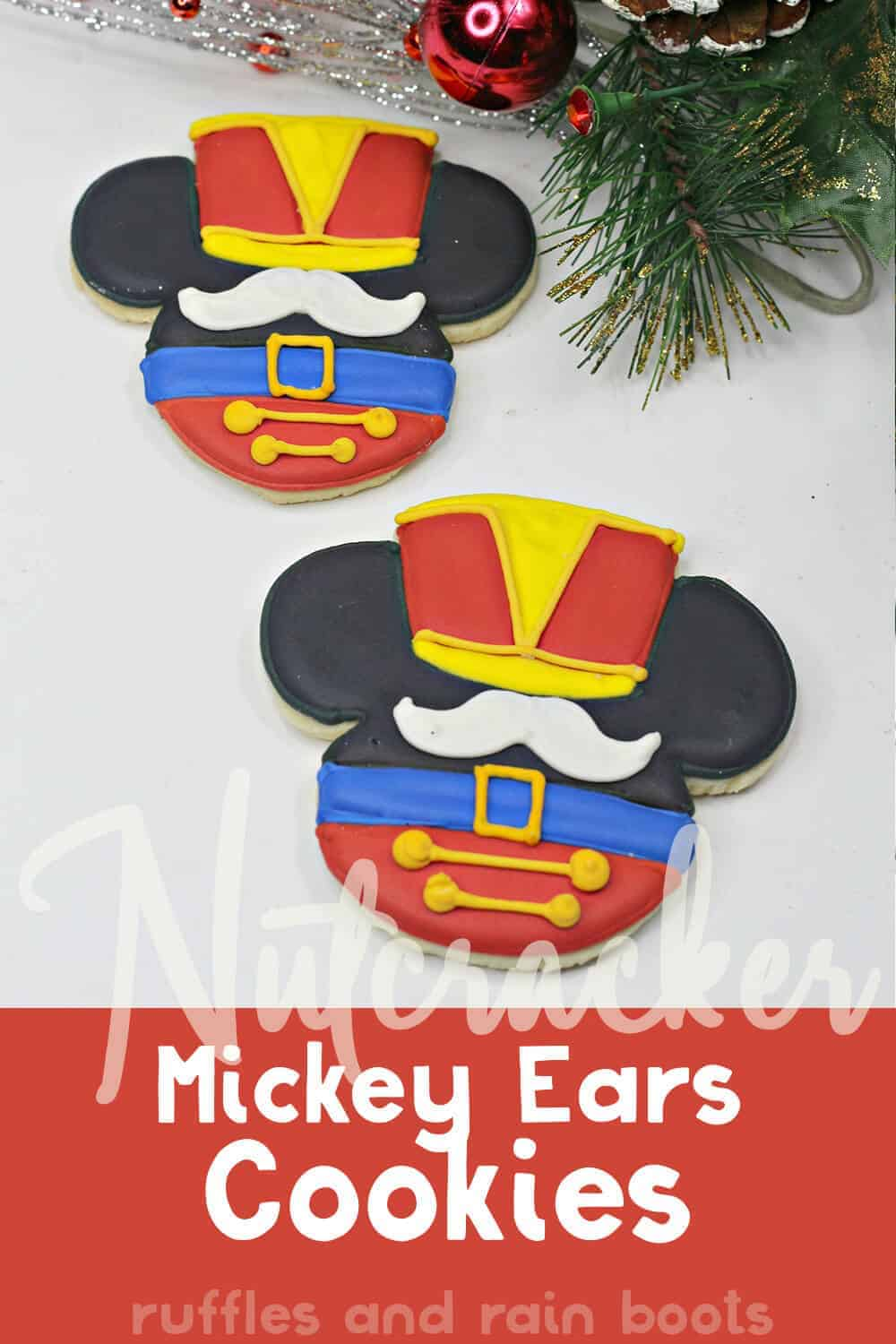 two sugar cookies decorated with Mickey Mouse ears dressed as a nutcracker with text which reads nutcracker mickey ears cupcakes