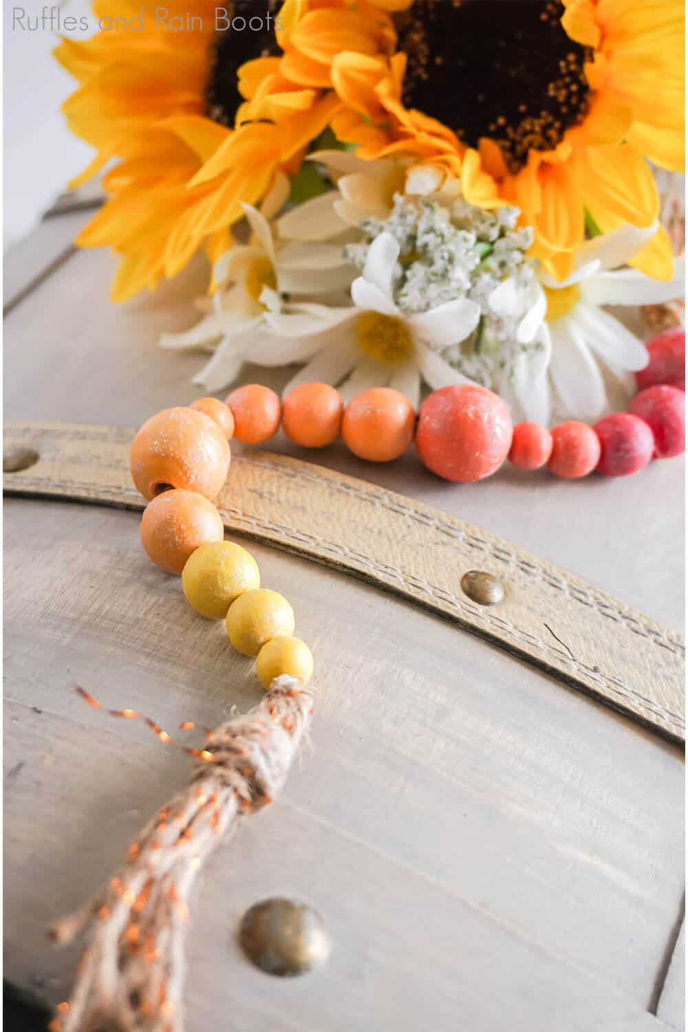 overhead view of ombre summer farmhouse beads on a light brown wood background with sunflowers