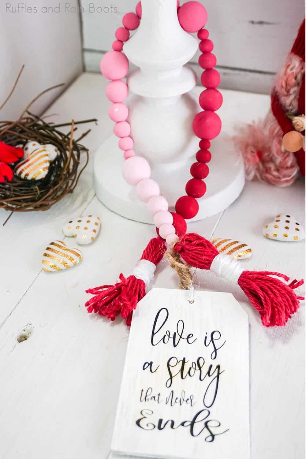 pink to red ombre farmhouse bead diy for valentines on a white table with a white candle holder