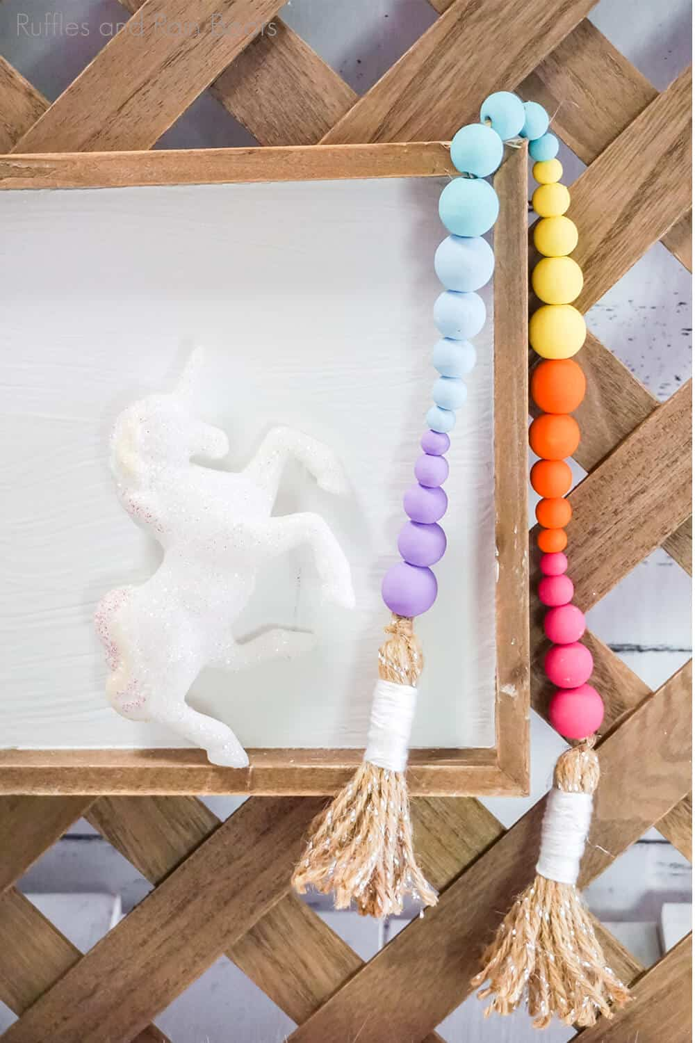 farmhouse beads painted in pastel colors hanging on a picture frame with a plastic unicorn