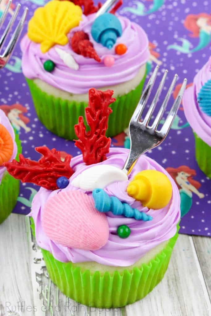 vertical image of 2 Princess Ariel cupcakes on an ariel image background