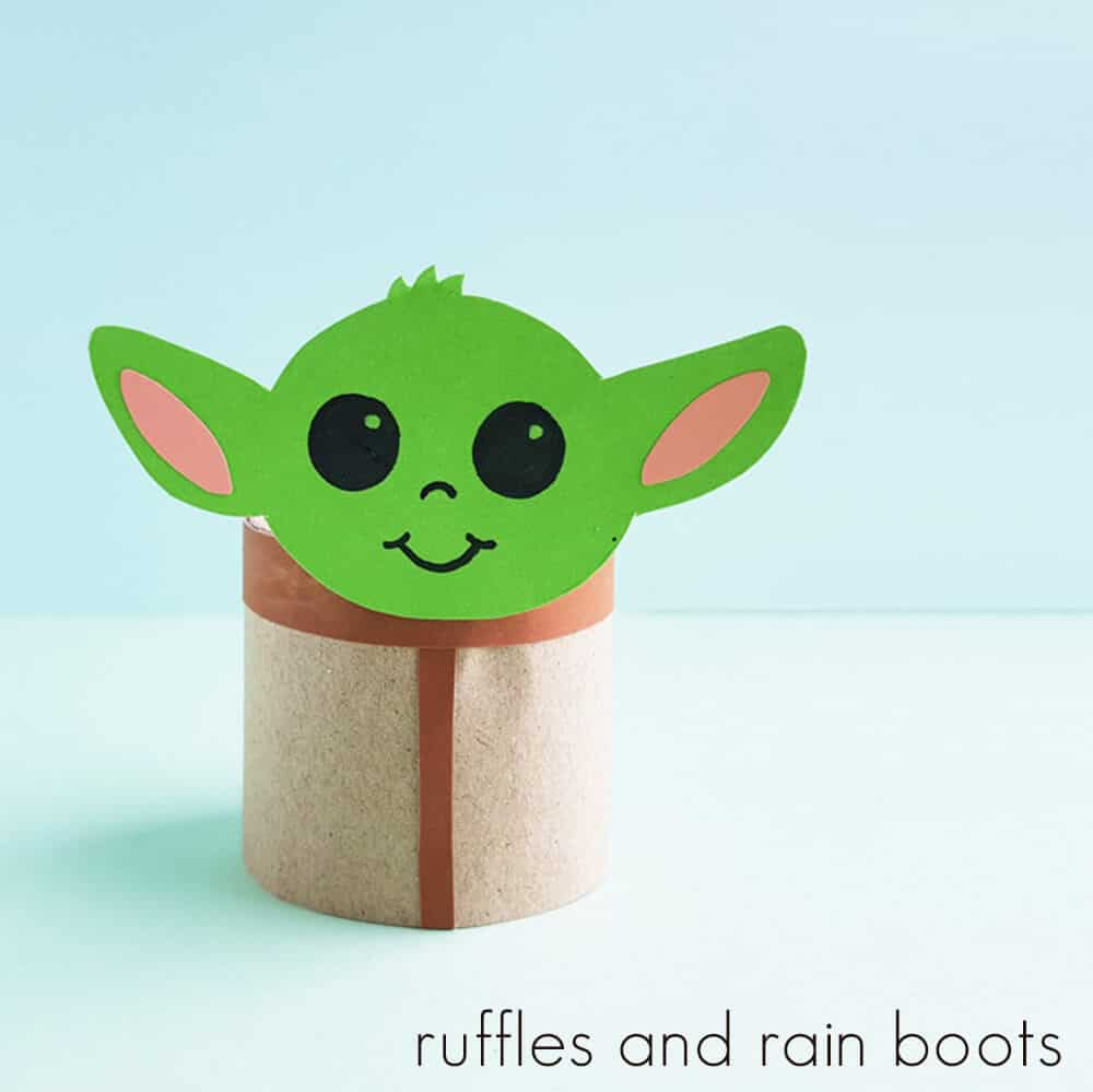 Square image of Baby Yoda Toilet paper craft finished on a light blue and green background.
