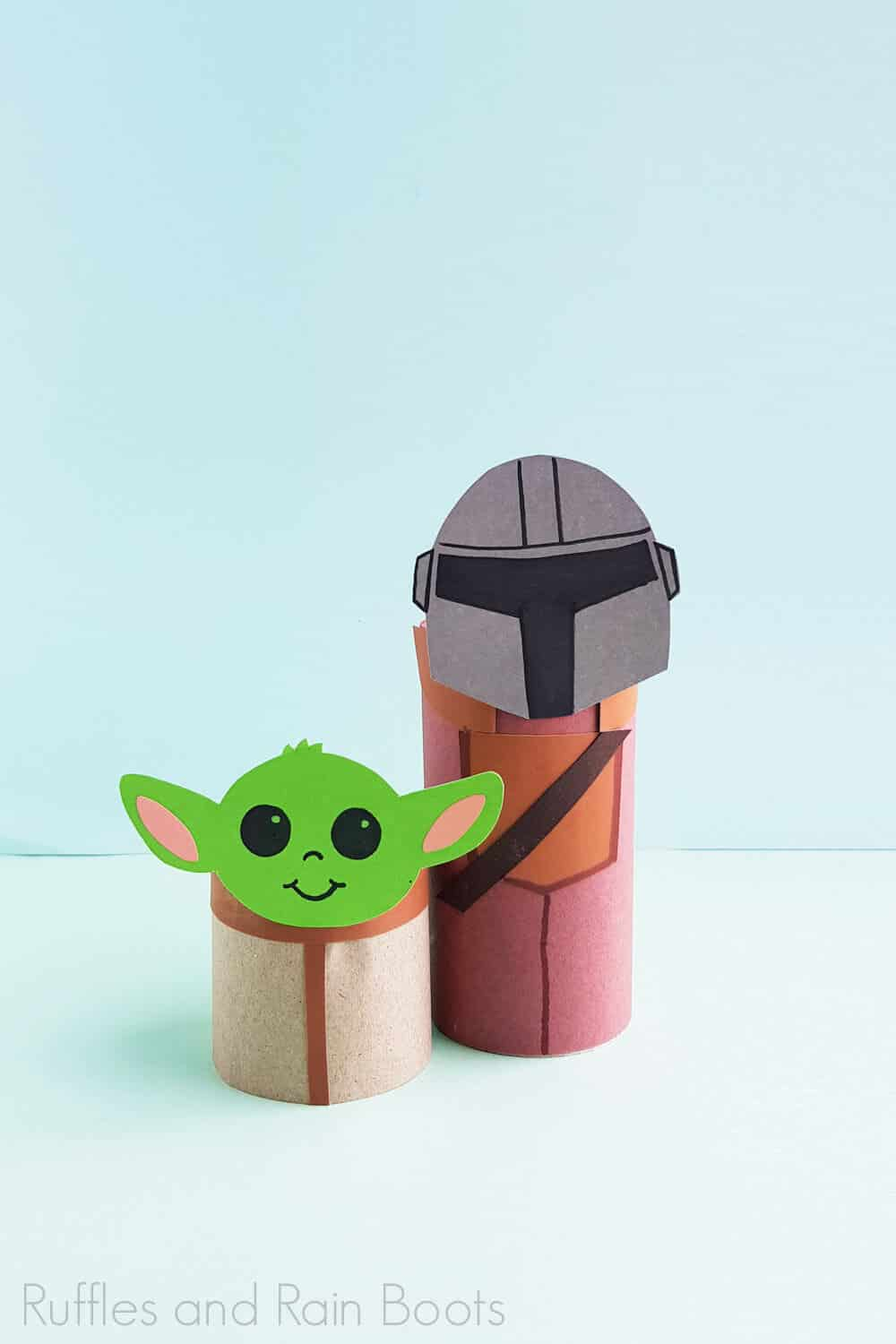 Vertical Image of finished Baby Yoda and the mandalorian paper craft on a light blue and green backgound