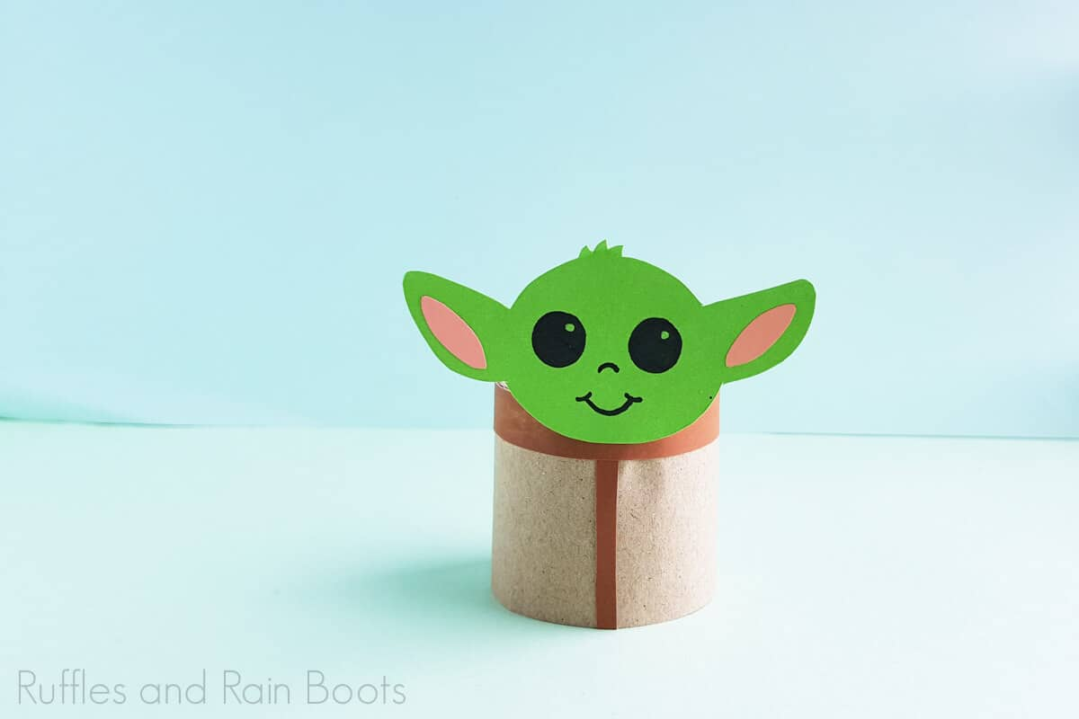 horizontal image of baby yoda toilet paper craft that is put together and on a blue and green background