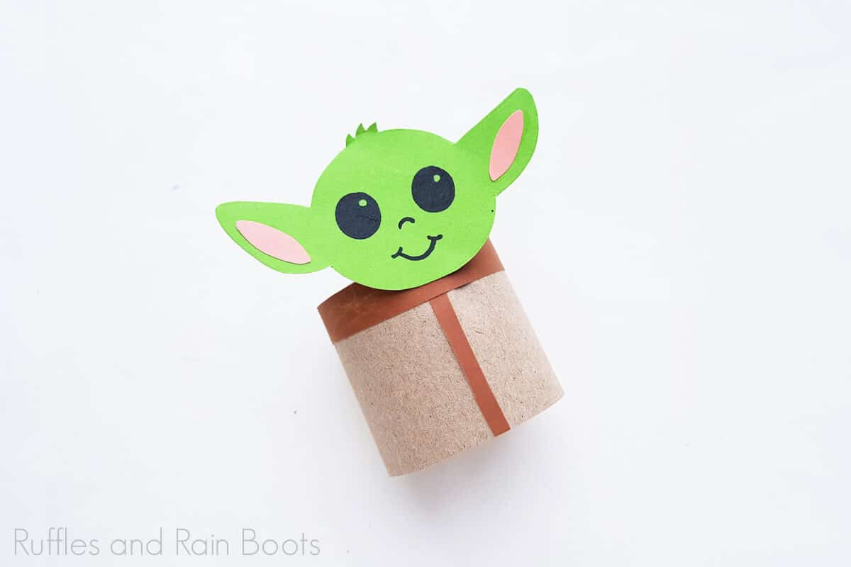Horizontal image of a finished baby yoda toilet paper craft on a white background.