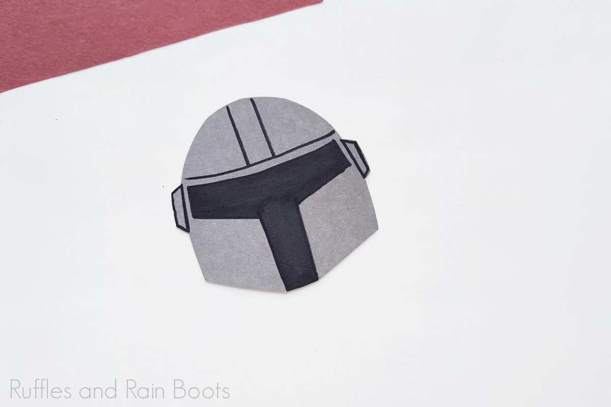 Process image of the mandalorian helmet put together on a grey background.