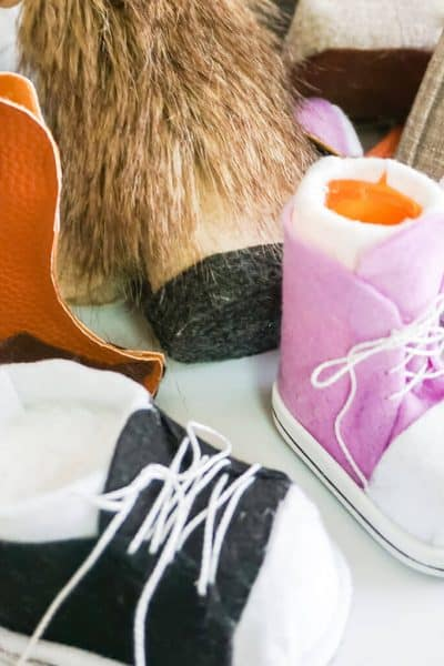 several gnome boots and gnome shoes on a white table