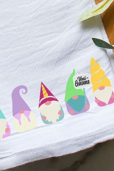overhead view of kitchen towel with sublimation gnome with unicorn theme on it