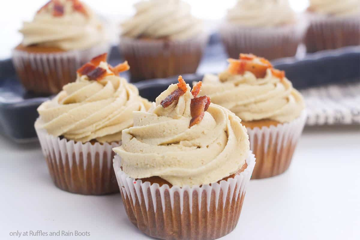 three easy maple bacon cupcakes on a white table