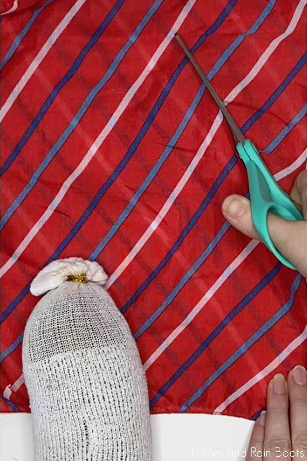 in-process step of cutting fabric to make a dollar store gnome for july 4th