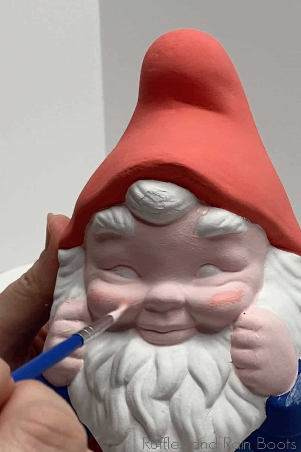 in-process step of painting cheeks on to illustrate steps to restore a garden gnome