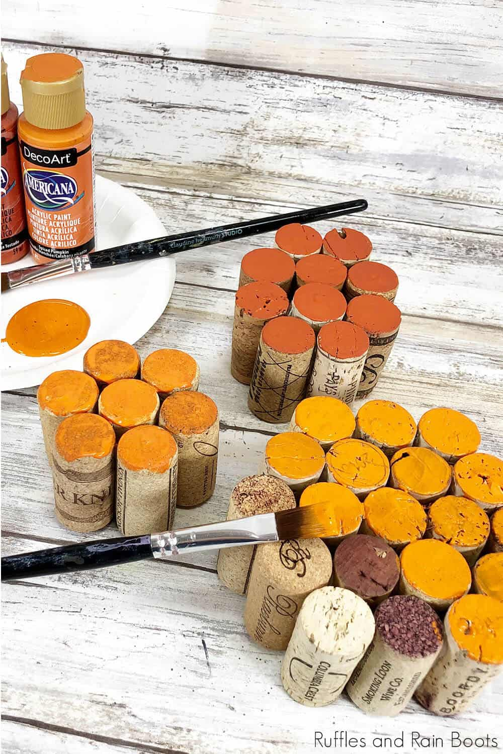 in-process step of painting glued corks to make a diy wine cork pumpkin craft
