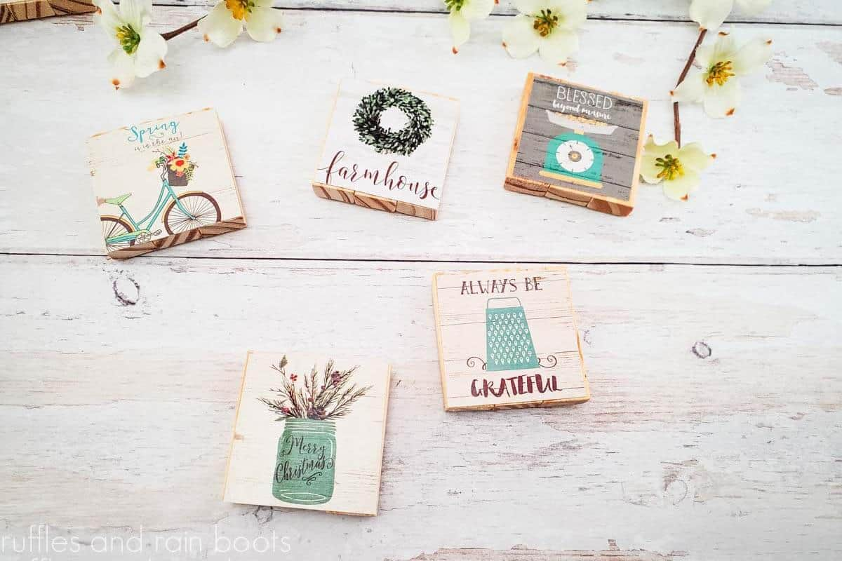 horizontal image of 5 dollar tree magnets made with the farmhouse calendar and tumbling tower blocks on a white wood background with small yellow flowers accenting the top of the image