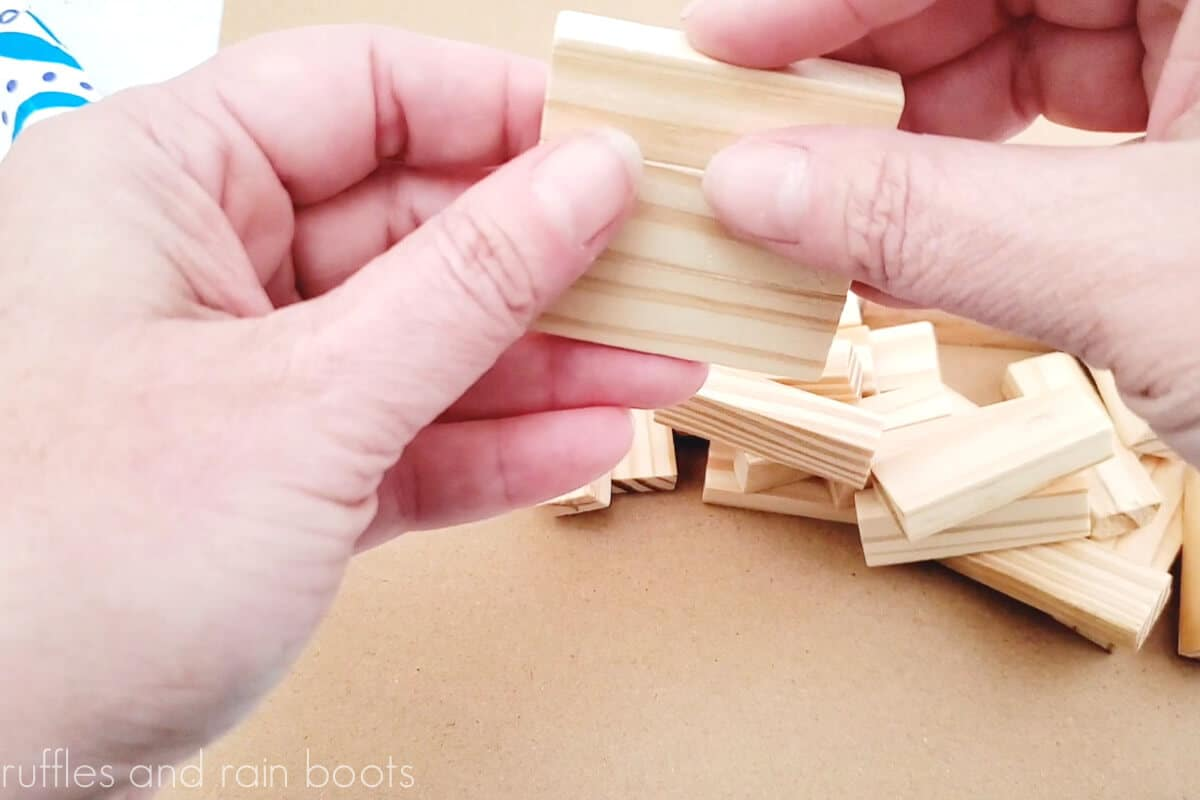 horizontal image of hands using wood glue to secure the dollar tree tumbling blocks together in a stack of three for the magnet base
