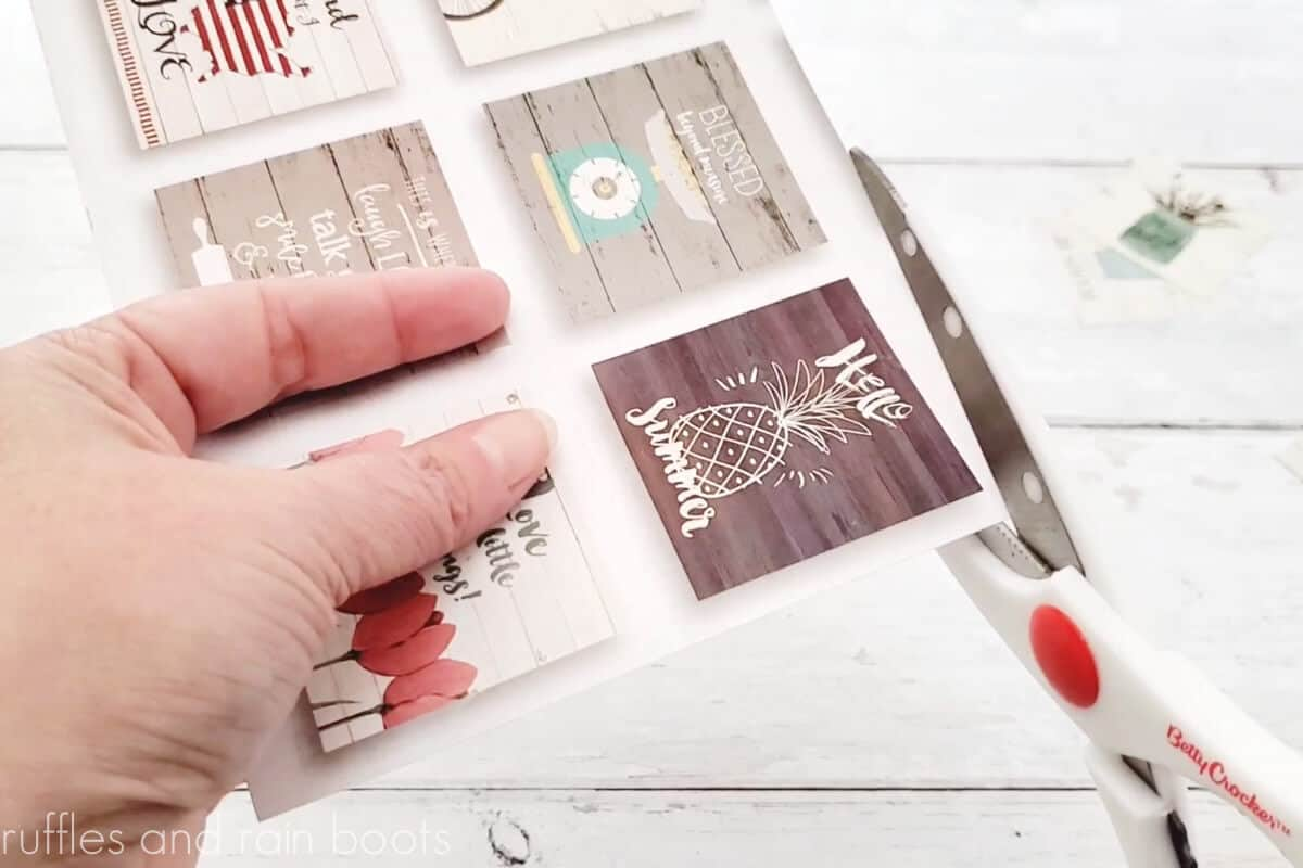 horizontal image of scissors cutting the back of the dollar tree farmhouse calendar images into small squares