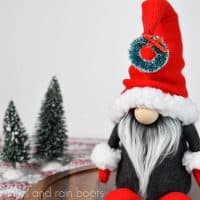 square image of a close up of a Scandinavian gnome with Nordic details of a gnome with arms and legs and a scrunched hat with a large nose in front of a Swedish style holiday background