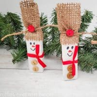 square image of 2 snowmen ornaments made with tumbling tower blocks from dollar tree painted white and given rustic burlap hat red ribbon scarf and buttons in front of Christmas greenery